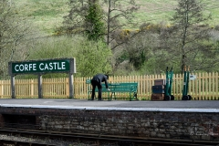 Guard cleaning a bench at Corfe Castle Railway Station.