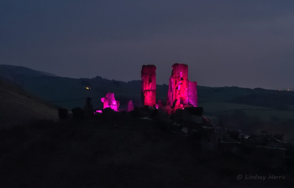Corfe Castle lit up in purple