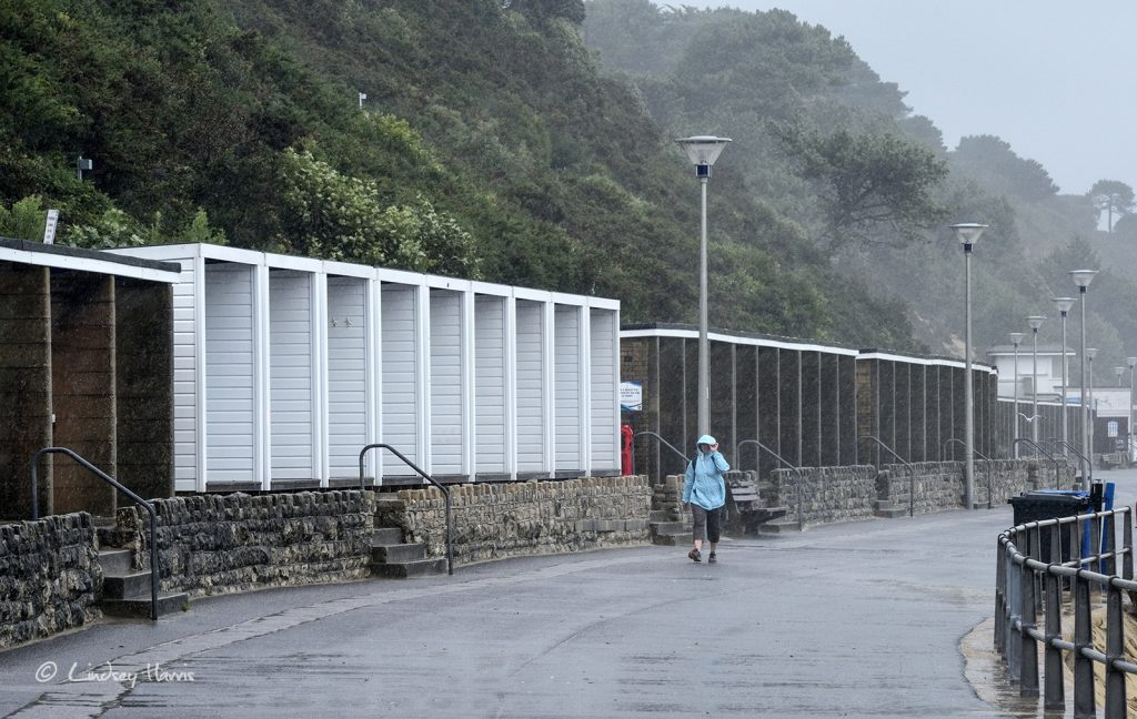 A lady walks along the promenade in driving rain and wind. Near Flaghead beach, Poole, Dorset.