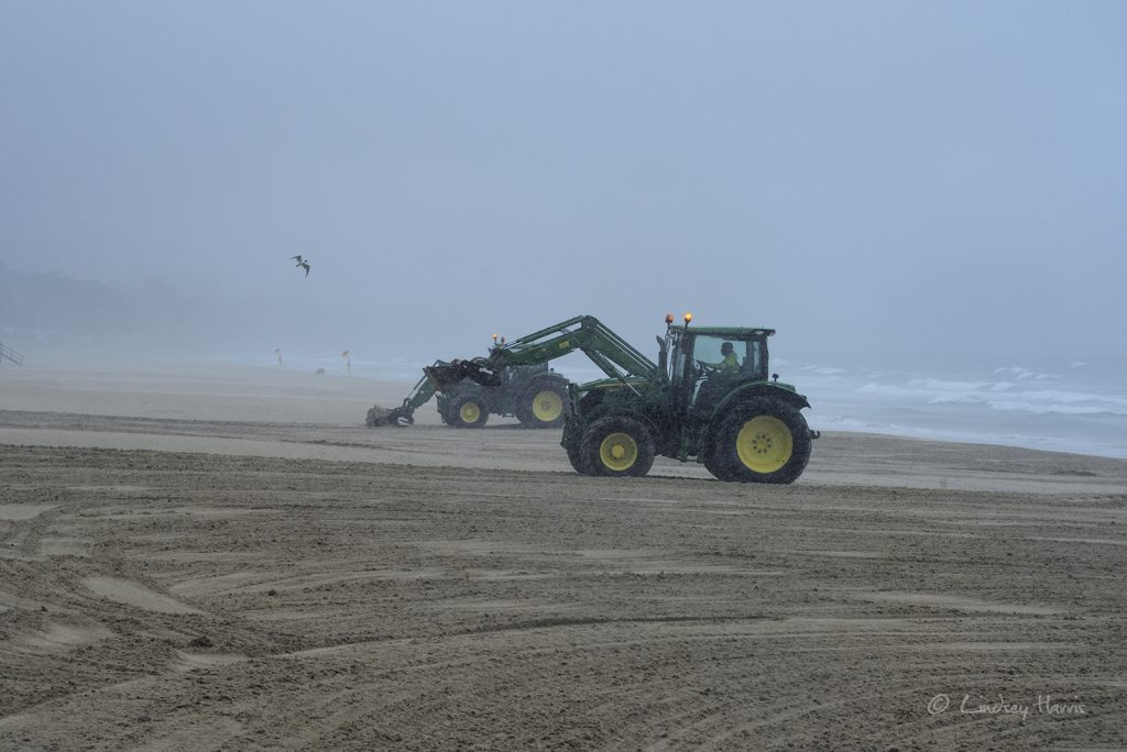 Tractors raking the beach during stormy weather. At Flaghead beach, near Sandbanks, Poole.  2nd August 2017.