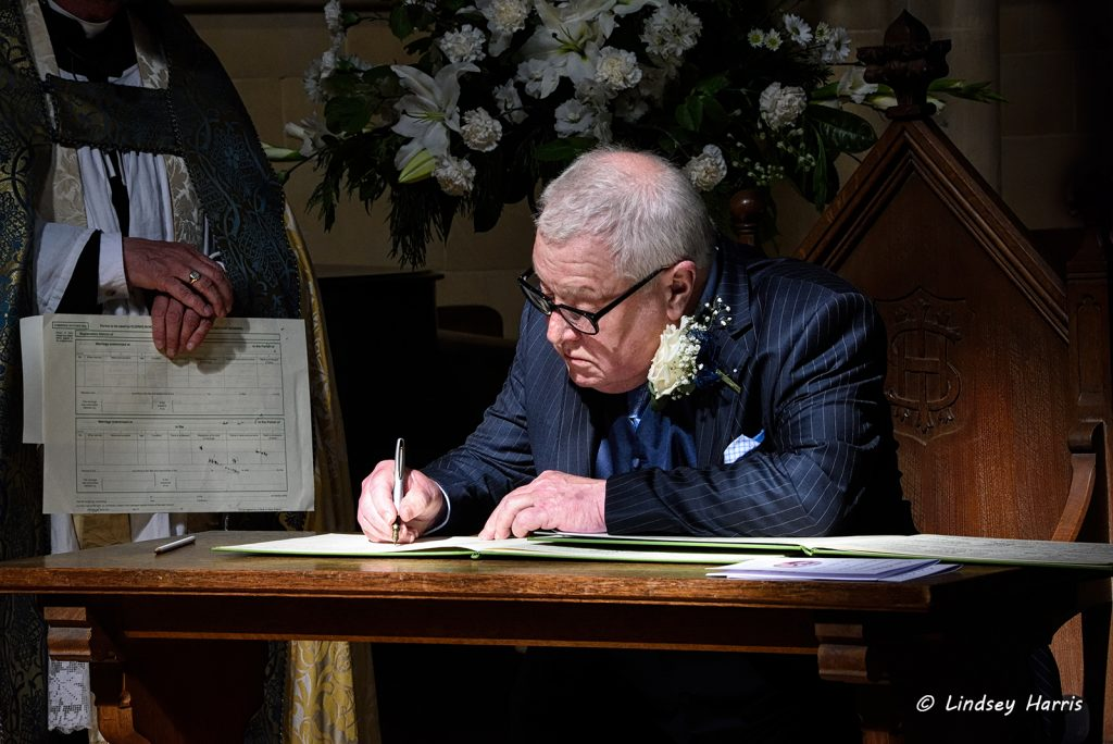 Photo of father of the bride signing The Register