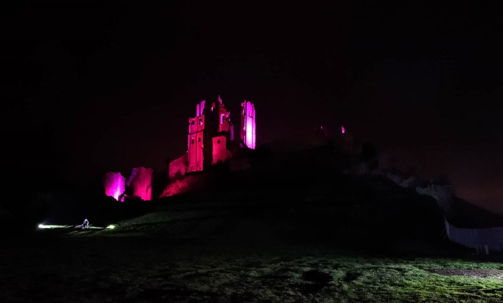 Corfe Castle lit up in purple. Purple Corfe Castle.