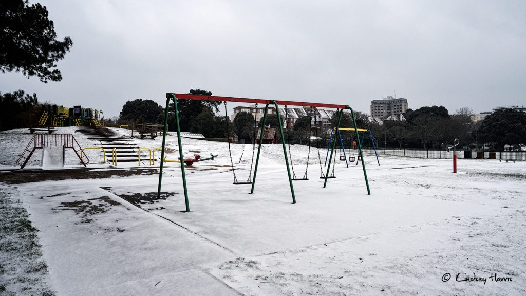 Deserted play area in the snow at Poole Park, Poole.