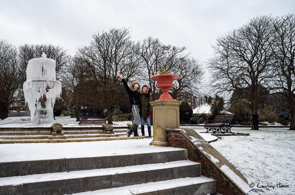 Two people pose for a selfie in the snow by the frozen fountain at Poole Park, Dorset.
