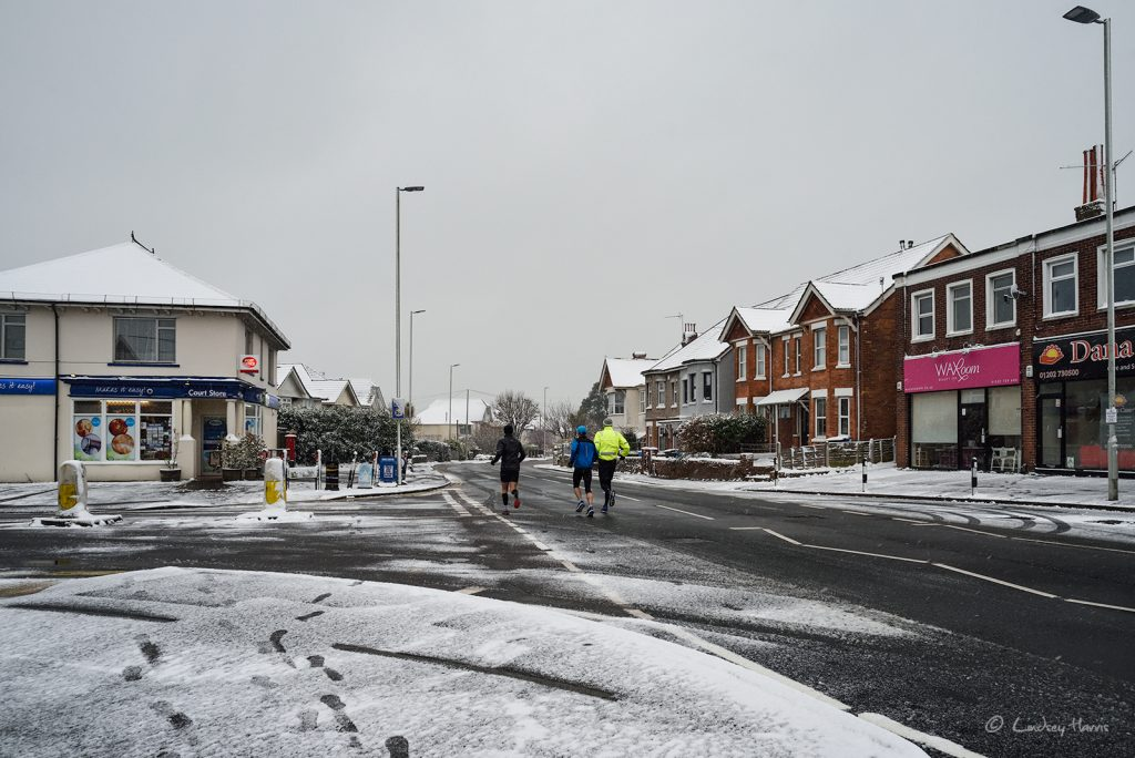 Runners take advantage of a deserted snowy Sandbanks Road, Poole. 18th March 2018.