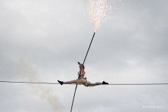 Phoebe balances on the tightrope with a pole and fireworks during Equilibrius.